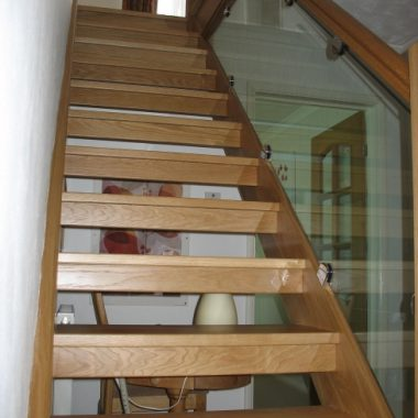 Close String staircase with open risers and clear glass balustrade